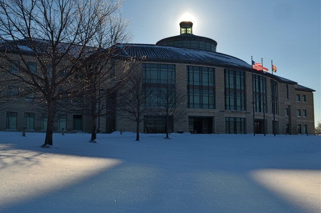 The rising sun transfers a greenish hue from the cupola atop the James Kirkpatrick Library down to the cold fresh snow below.